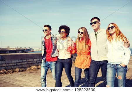 tourism, travel, people and leisure concept - group of happy teenage friends walking along city street
