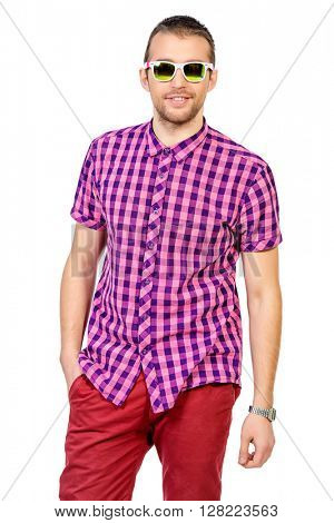 Happy young man in stylish bright clothes posing at studio. Summer fashion.