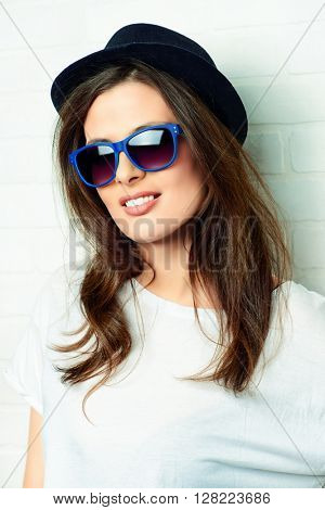 Modern young woman in sunglasses and a hat stands by a brick wall and smiling.