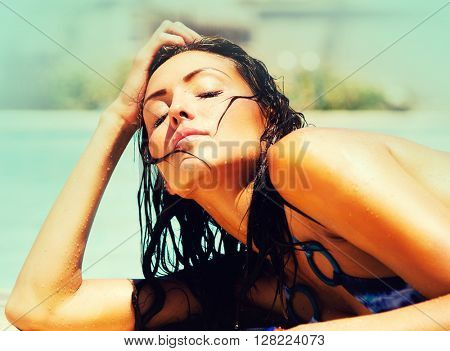 Beautiful woman beside swimming pool basking in the summer sun