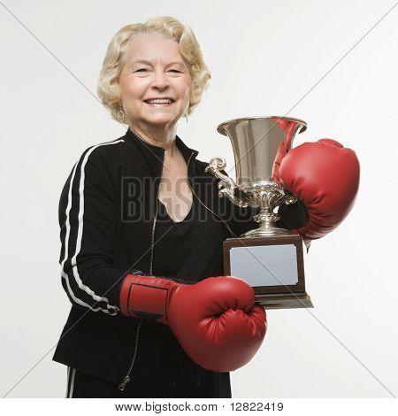 Caucasian senior Woman tragen Boxhandschuhe, die Trophäe zu halten.