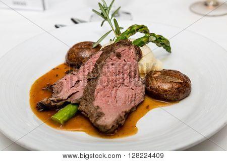 A dinner of sliced beef tenderloin mashed potatoes asparagus and mushroom gravy