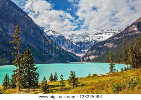 Magnificent Lake Louise is surrounded by mountain peaks and glaciers. Rocky Mountains, Canada, Banff National Park. Great sunny day