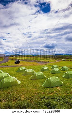Scenic camp on a green meadow. Summer holidays in Iceland