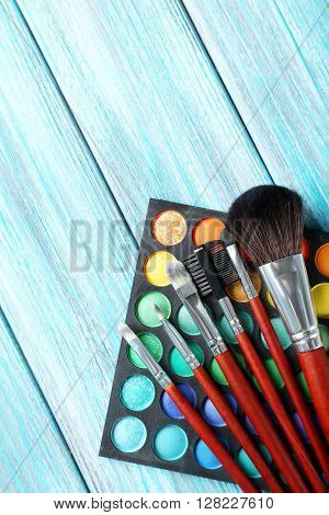 Makeup Brushes And Cosmetics On Blue Wooden Table