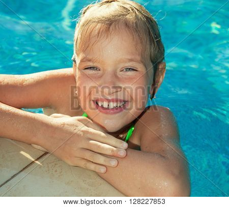 Happy child at pool outdoors. Girl playing at summer. Tourist