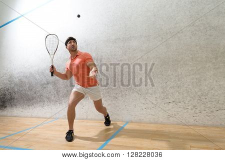 Young squash player hiting ball in squash court. Handsome man in orange t-shirt and white shorts playing popular game in squash.