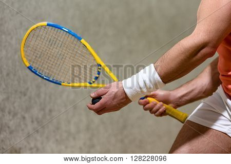 Half closeup picture of squash racket in man's hands. Muscular man playing squash on court indoors.