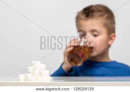 Glass full of soft drink next to it is the amount of sugar used in it. Shallow DOF on sugar cubes.