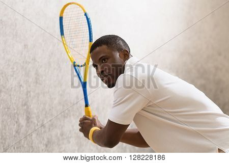 Squash player man posing with racket on court. Handsome black athlete doing sport indoors. Cute young man looking in distance.