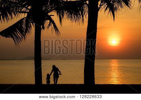 Beautiful sunset on beach with caring happy mother and daughter walking under coconut tree in silhouette twilight golden hour/Sunset on beach, happy mother and daughter