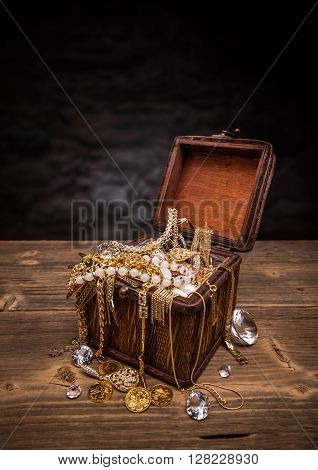 Open treasure chest full of jewellery, studio shot