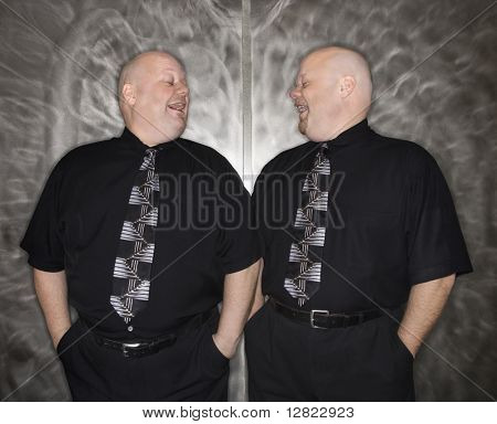 Caucasian bald mid adult identical twin men looking at each other laughing.