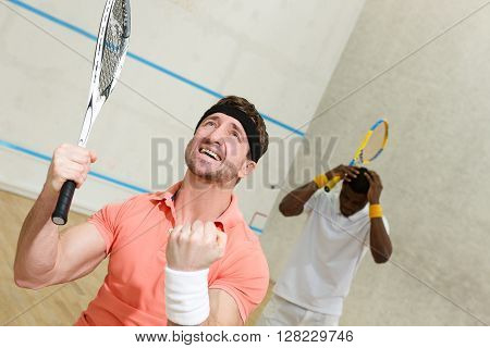 Handsome squash player man expressing astonishment after great battle in squash with his best friend on court.