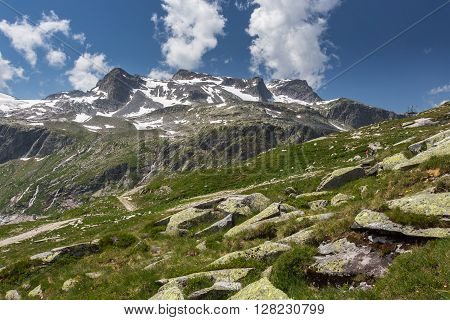 View of mountains in summer. Snow-capped mountains in Austrian Alps. Sky with clouds. Hill overgrown with grass in foreground. People walking along hiking trail