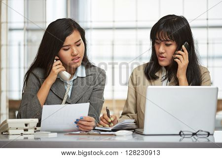 two businesswomen communicating with their clients on the phone