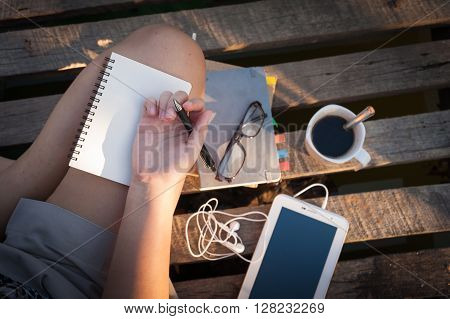 Young hipster woman writing journal on small notebook while sitting on wood litter in early morning time on weekend