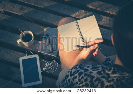 Young hipster woman writing journal on small notebook while sitting on wood bridge in early morning time on weekend with high contrast sun lighting and vintage filter effect