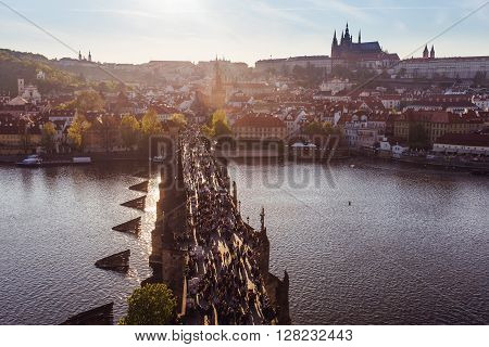 Prague Charles Bridge from above Vltava River Prague Castle. The historic center of Prague at sunset in the spring. Soft light. People walking on the Charles Bridge. Romance in Prague