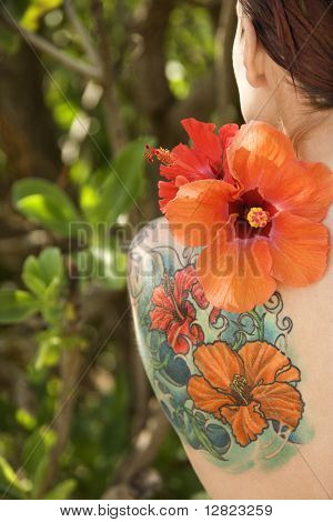Back view of tattooed Caucasian woman with Hibiscus flower over her shoulder in Maui, Hawaii, USA.