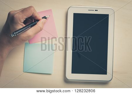 Young man writing with left hand on pink sticky paper beside small tablet pc with blank area on touchscreen on wood table with vintage filter effect