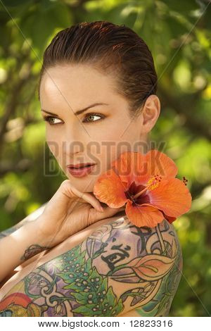 Attractive Caucasian tattooed woman with Hibiscus flower over her shoulder in Maui, Hawaii, USA.