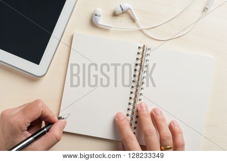 Young man left hand writing on notebook beside small tablet pc and in ear headset on wood table