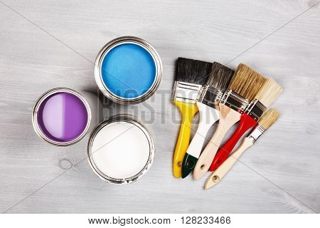 House renovation, paint cans and colored brushes on white wooden background