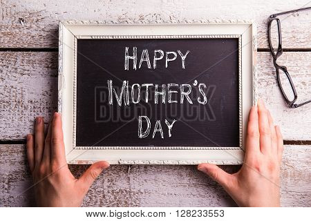 Hands of unrecognizable woman holding picture frame with Happy Mothers Day note. Eyeglasses. Studio shot on white wooden background.