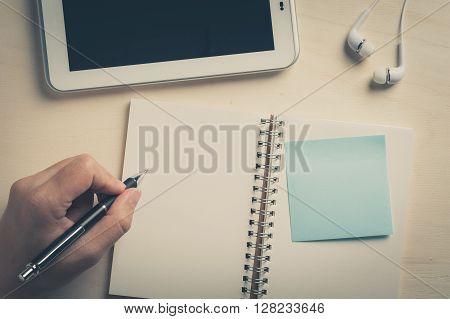 Young man left hand writing on notebook with sticky paper beside small tablet pc and in ear headset on wood table with vintage filter effect