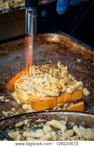 London United Kingdom - April 30 2016: Maltby Street Market in Bermondsey (located in railway arches SE1 Rope Walk). Great artisan street food stalls and bars. Flame grilled sandwich with Macaroni and cheese