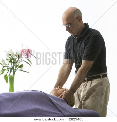 Caucasian middle-aged male massage therapist massaging face of Caucasian middle-aged woman lying on massage table.