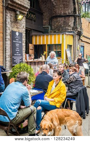 London United Kingdom - April 30 2016: Maltby Street Market in Bermondsey (located in railway arches SE1 Rope Walk). Great artisan street food stalls and bars. People are enjoying their afternoon