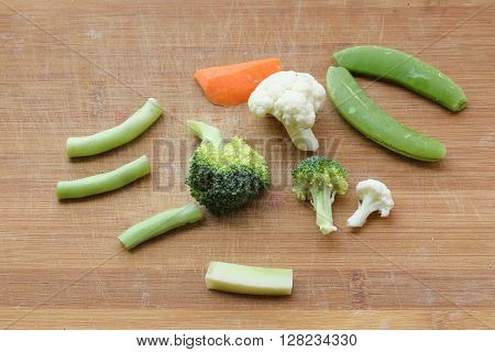 Mixed vegetable cut sliced chopped on wooden chopping board