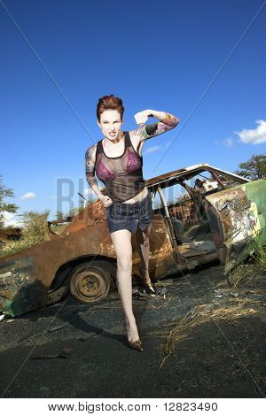 Sexy tattooed Caucasian woman standing with defiant look punching in front of old rusted car in junkyard.