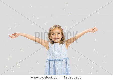 Cute little girl playing with soap bubbles