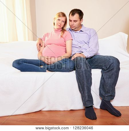 Couple With Pregnant Woman Relaxing On Sofa Together