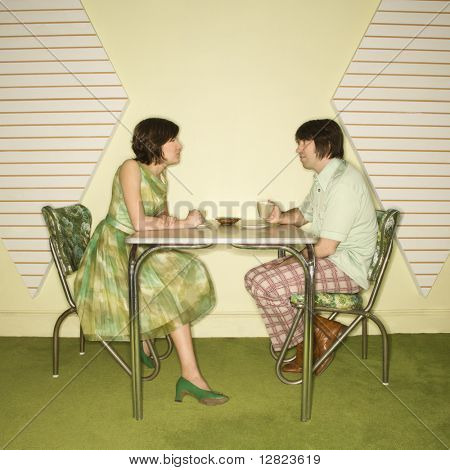 Caucasian mid-adult man and woman wearing vintage clothing sitting at 50's retro dinette set facing each other.