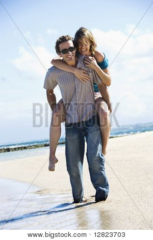 Mid-adult Caucasian man giving woman piggyback ride on beach.