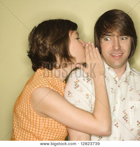 Pretty Caucasian mid-adult woman whispering into Caucasian mid-adult man's ear with surprized expression on face.