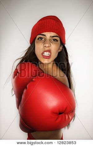 Caucasian woman wearing boxing gloves and hat.