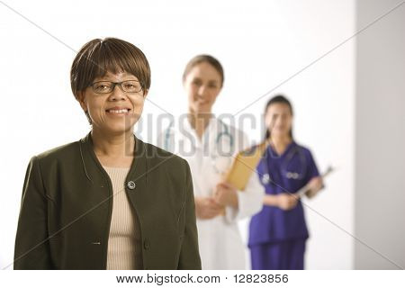 African American middle-aged woman smiling and looking at viewer with Caucasian mid-adult female doctor and Asian Chinese mid-adult female physician's assistant standing in background.