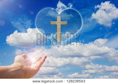 Crucifix and light on heart background with hand
