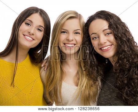 Studio portrait of three beautiful teenage girls smiling