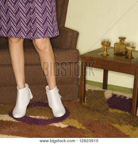 Close-up of standing Caucasian mid-adult female legs in vintage clothing.