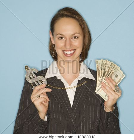Caucasian businesswoman smiling holding money and wearing necklace with oversized dollar sign.