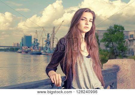 Lonely girl waiting for your. Wearing light gray shirt, black jacket, an young american woman standing by metal fence on pier in New York, frowned, with port cranes on background. Instagram effect.