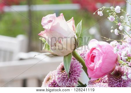 Pastel rose in a bouquet of flowers on a terrace