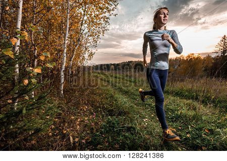 Woman in sportswear running along the path in autumn forest