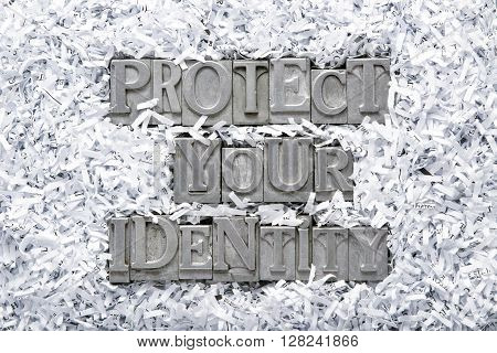 protect your identity phrase made from metallic letterpress type inside of shredded paper heap